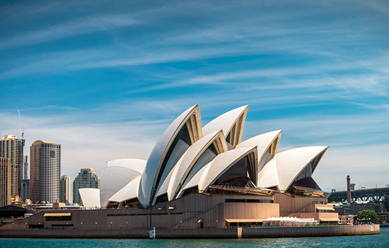 Sydney opera house from water with big city in background and bridge in summer