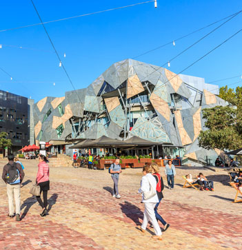 people walking through Federation Square looking at buildings